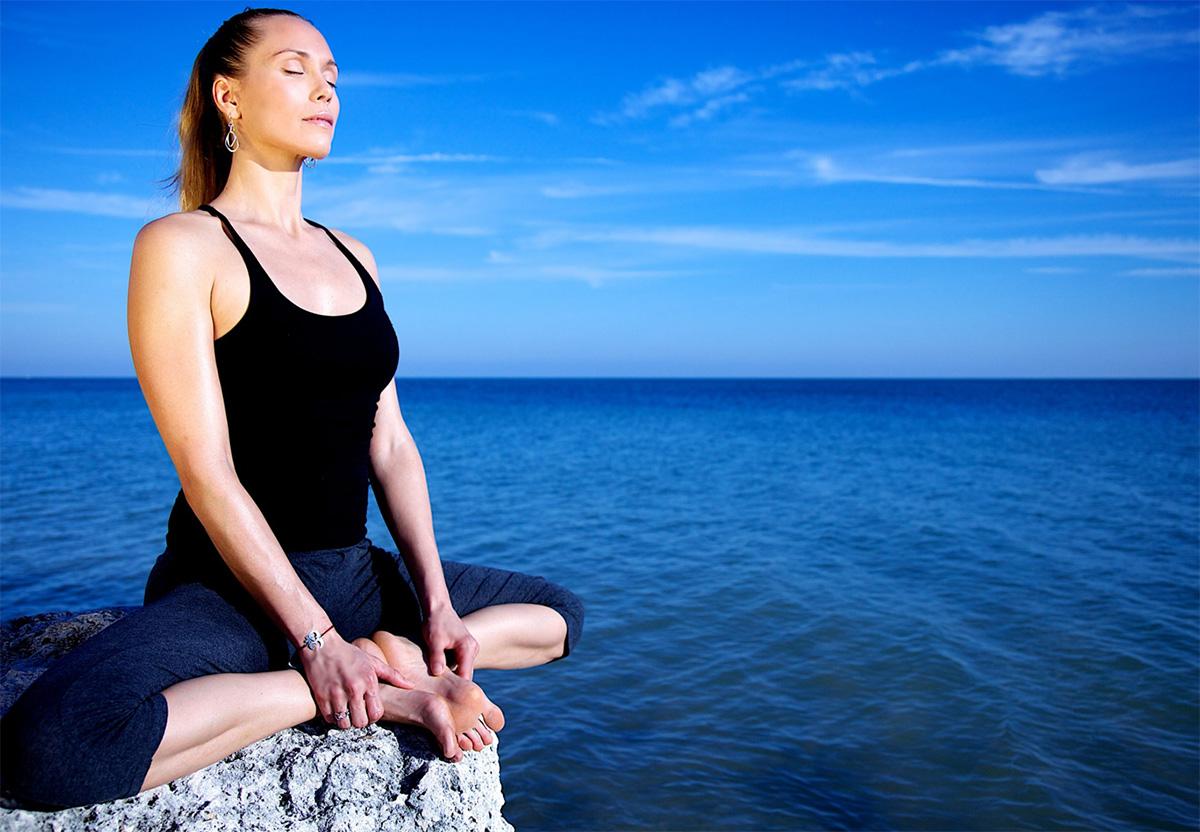 rae indigo meditating on rocks by the ocean